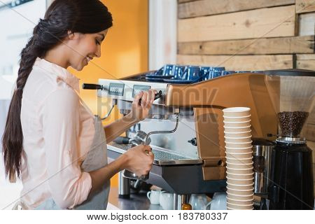 Waitress using coffeemaker in cafe