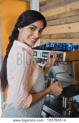 Portrait of waitress using coffeemaker in cafe