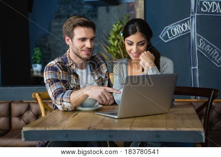 Young couple using laptop while having coffee in café