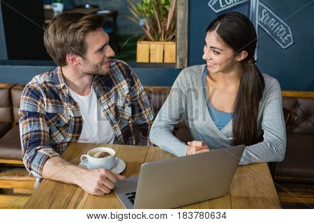 Young couple interacting while having coffee in café