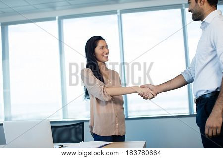 Smiling business people shaking hands during meeting at office conference room