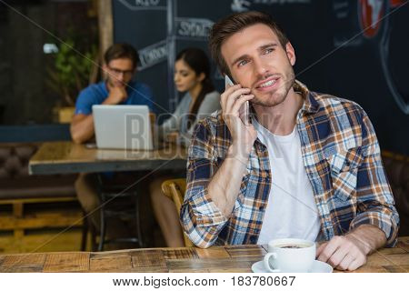 Man talking on mobile phone while having coffee in café
