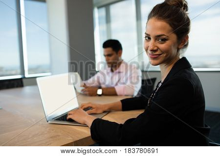 Businesswoman typing on laptop at table with male colleague using digital tablet in background