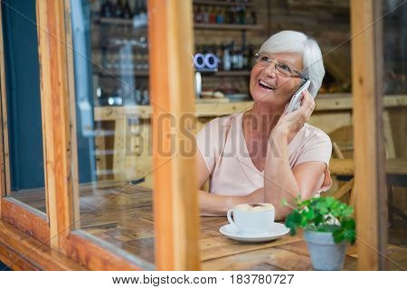 Senior woman talking on mobile phone while having coffee in café