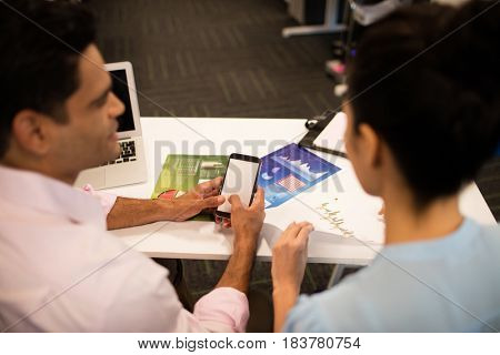 Rear view of business colleagues sitting together at desk in office