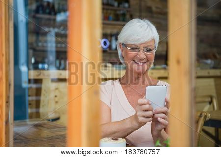 Senior woman using mobile phone while having coffee in cafe