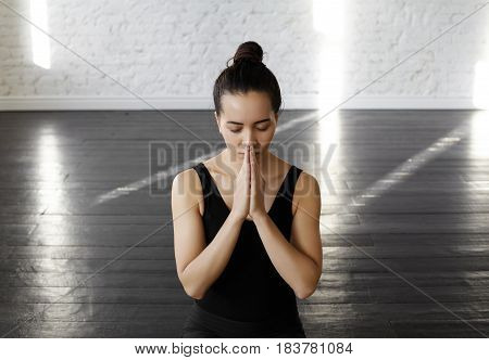 Pretty asian young woman holding hands in namaste or prayer keeping eyes closed while practicing yoga and meditating at yoga class early morning having calm look on her face. Keep calm in a big city