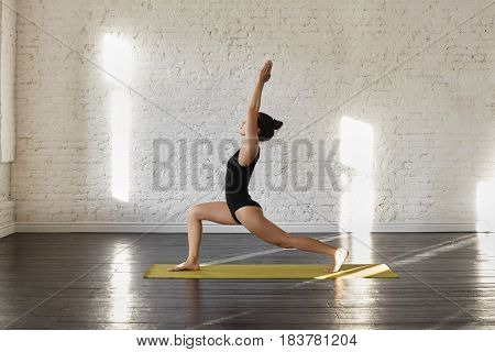 Sporty asian young woman doing yoga practice at green yoga mat in training class in the morning. Portrait of an exercise-focused asian female practicing stretching looking aside. Yoga concept