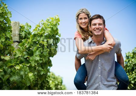 Portrait of happy young couple piggybacking at vineyard against blue sky