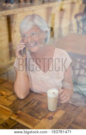 Happy senior woman talking on mobile phone while having cold coffee in cafe
