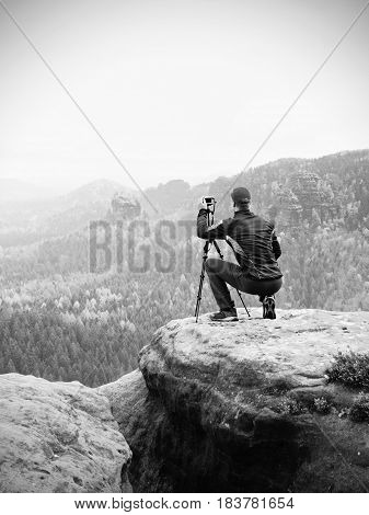 Outdoor Photographer With Tripod And Camera On Rock Thinking. Autumnal Valley