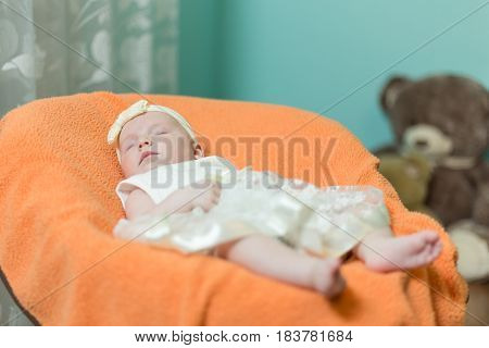 Infant sleeps in the armchair for toddlers. Baby is dressed in a beautiful dress.