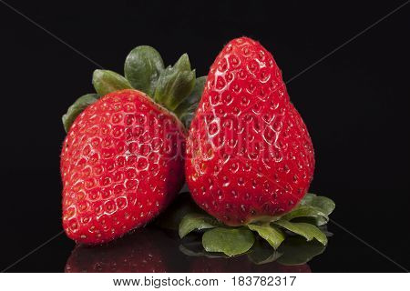 Fresh fruits of red strawberry isolated on black background close up.