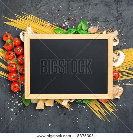 Blank board chalk with set of ingredients for cooking Italian pasta on a dark surface top view
