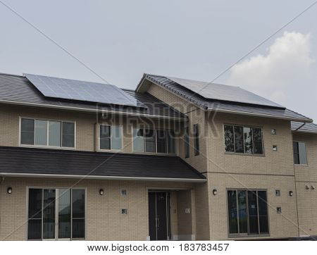 Solar panels on roof of a house with cloudy sky background