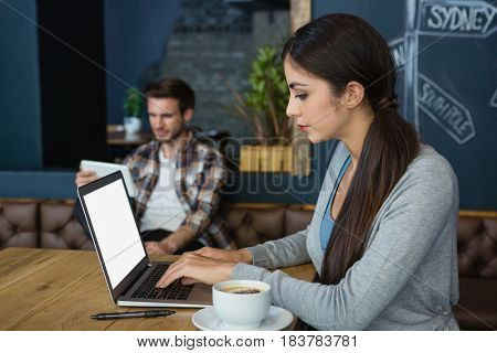 Young woman using laptop while having coffee in cafe
