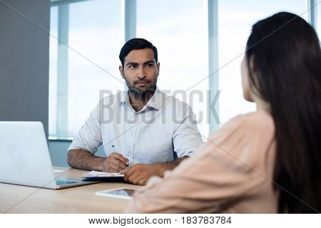 Business people discussing over contract in conference room
