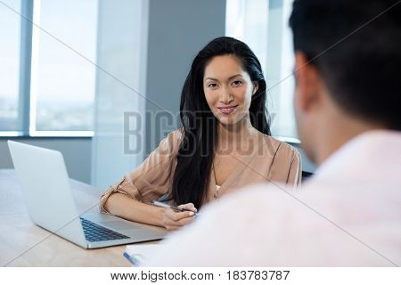 Young businesswoman sitting with male colleague at table in office