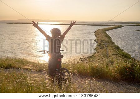 Happy boy with open arms riding his bike at sunset, enjoying the nature, beautiful trail winding ahead through the bay.