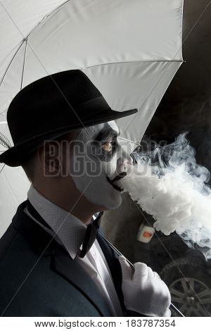 Scary evil clown wearing a bowler hat vaping