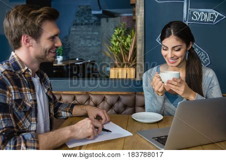 Young couple interacting while having coffee in cafe