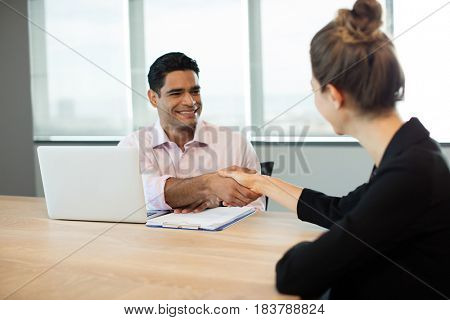 Business people shaking hands during meeting in conference room