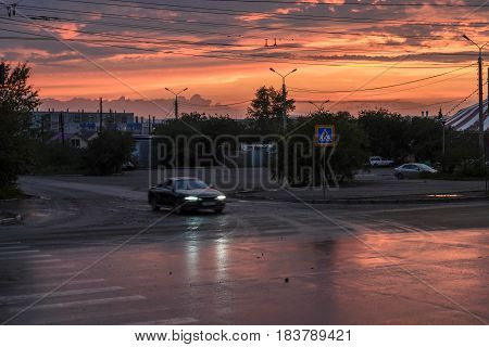 Colorful and red sunset illuminates the road in the city. Beautiful sky at sunset.