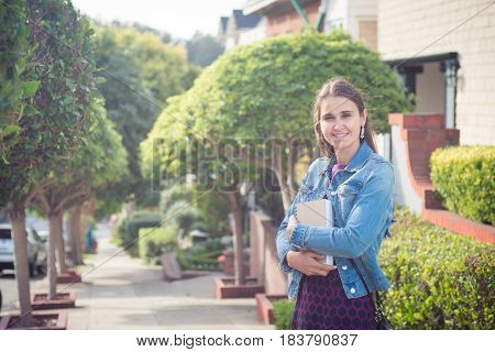 Young attractive woman standing with books in sunny street, smiling confidently