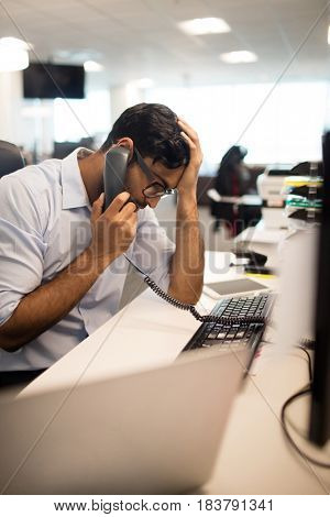 Tensed businessman with head in hand talking on land line at desk in office