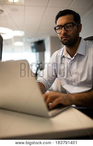 Young businessman working on laptop while sitting at desk in office