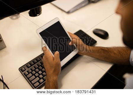 Cropped image of businessman using digital tablet while sitting at desk in office