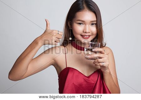 Young Asian Woman Thumbs Up With A Glass Of Drinking Water.
