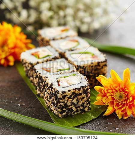 Chicken Maki Sushi - Sushi Roll made of Smoked Chicken Breast, Cheese, Fresh Tomato and Tamago (Japanese Omelet) inside. Sesame outside. Japanese Sushi Food and Natural Flower Concept