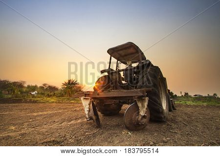 Tractor prepare soil for cultivation with beautiful sunset at agriculture field
