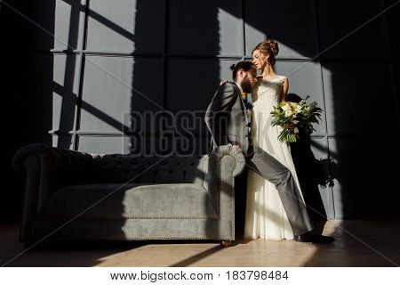 The Bride Is Hugging The Groom Sitting On The Arm Of The Sofa. They Are Lit By Hard Light From The W