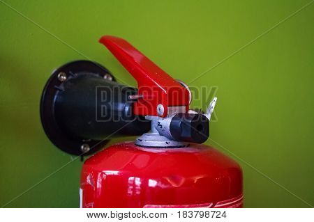 Close up of top part of red fire extinguisher with green background