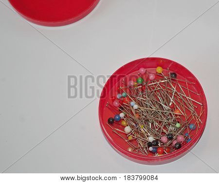 Dressmaking pins with plastic colored heads in a round red plastic container.