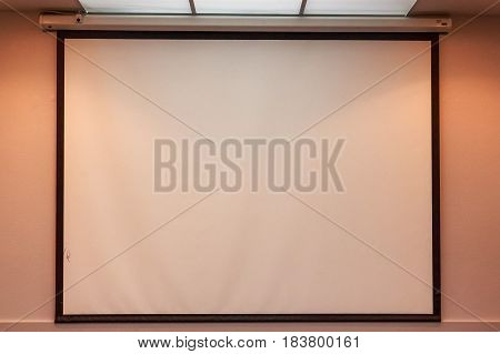 Close up white projection screen on beige wall