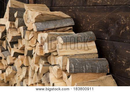 Pile of firewood next to the wooden cottage