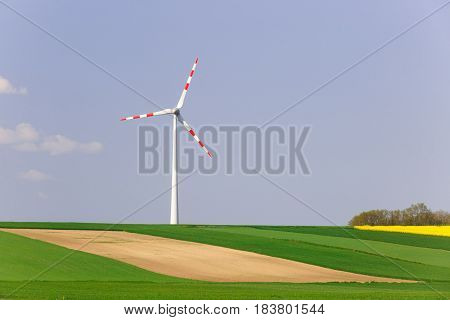Wind farm with spinning wind turbine amidst agricultural land of intensive crop production. Sustainable and renewable power production ecology and environmental conservation concept.