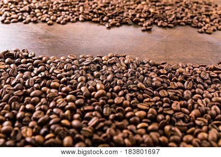 Close Up View Of Roasted Coffee Beans On Wooden Tabletop