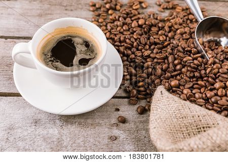 Close Up View Of Coffee Mug Steam And Beans With Scoop On Sack Cloth