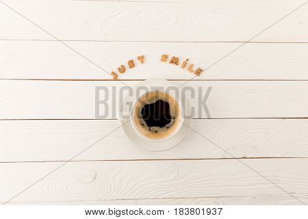 Top View Of Coffee Mug Steam And Just Smile Lettering On Wooden Table