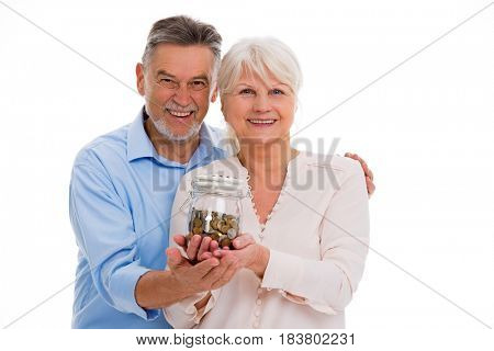 Senior couple with money in glass jar