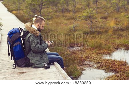 Handsome, bearded man with backpack texting in swamps. Camp, adventure, traveling and trip concept.