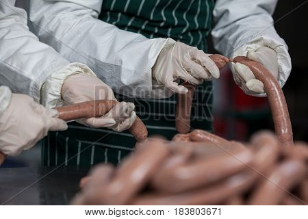 Midsection of butchers processing sausages at meat factory