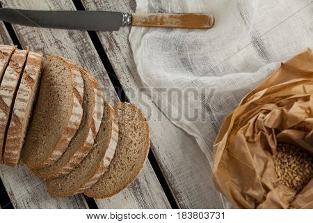 Sliced loaf of bread with knife on wooden background