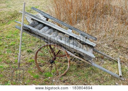 The old cart and pitchfork in the yard of the rural house