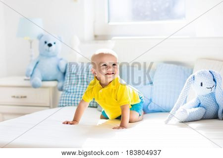 Baby playing on parents bed. Cute funny little boy learning to crawl in white sunny nursery. Infant and toddler room interior. Bedding and toys for kids. Children play at home. Baby bedroom.