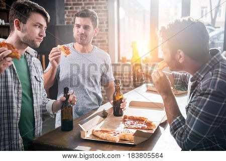Young People Having Fun While Drinking Beer And Eating Pizza At Home